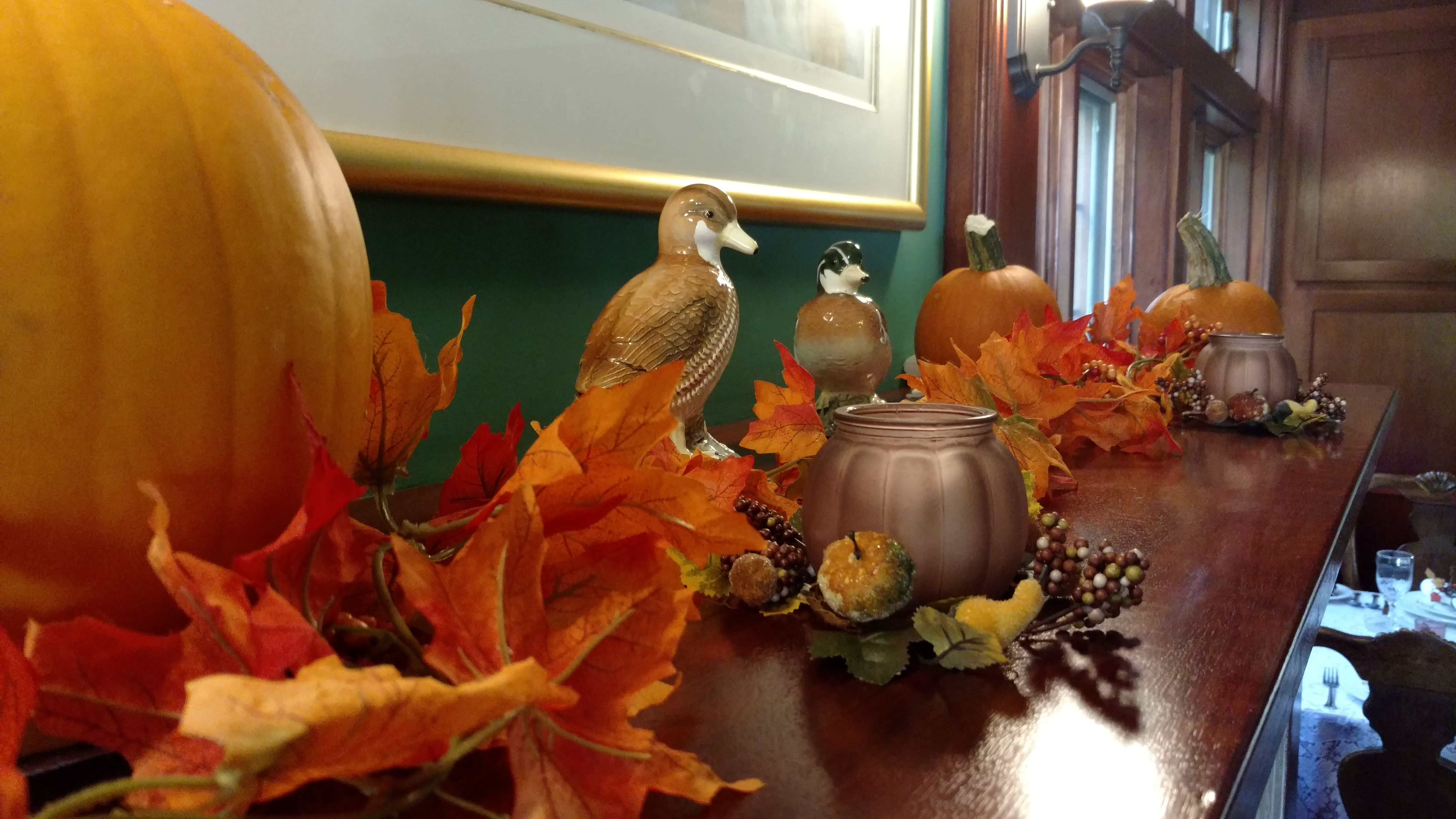 Fireplace mantle at Isaiah Jones Homestead B&B - decorated for fall with pumpkins, colorful silk maple leaves, and carved ducks.