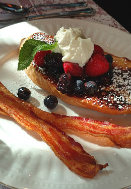 Breakfast plate with French toast topped with blueberries, black berries, strawberries, whipped cream and a sprig of mint with bacon on the side.